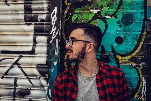 Cool guy with glasses in front of graffiti