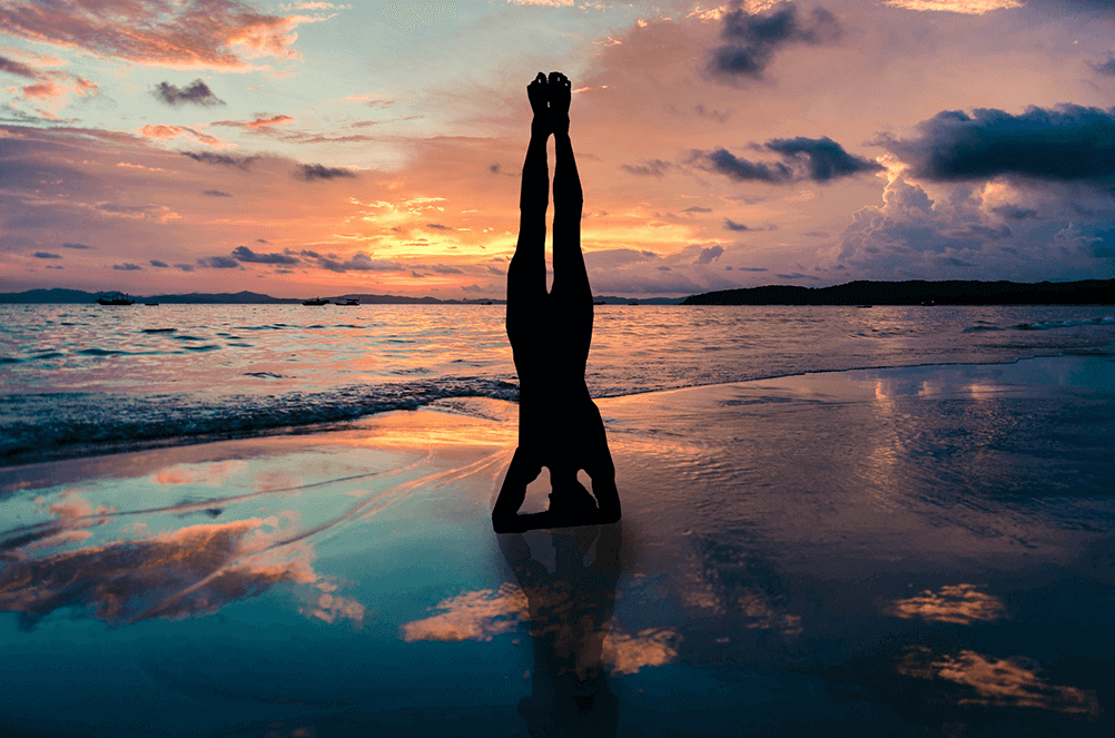 Young woman practices yoga on the beach at sunset