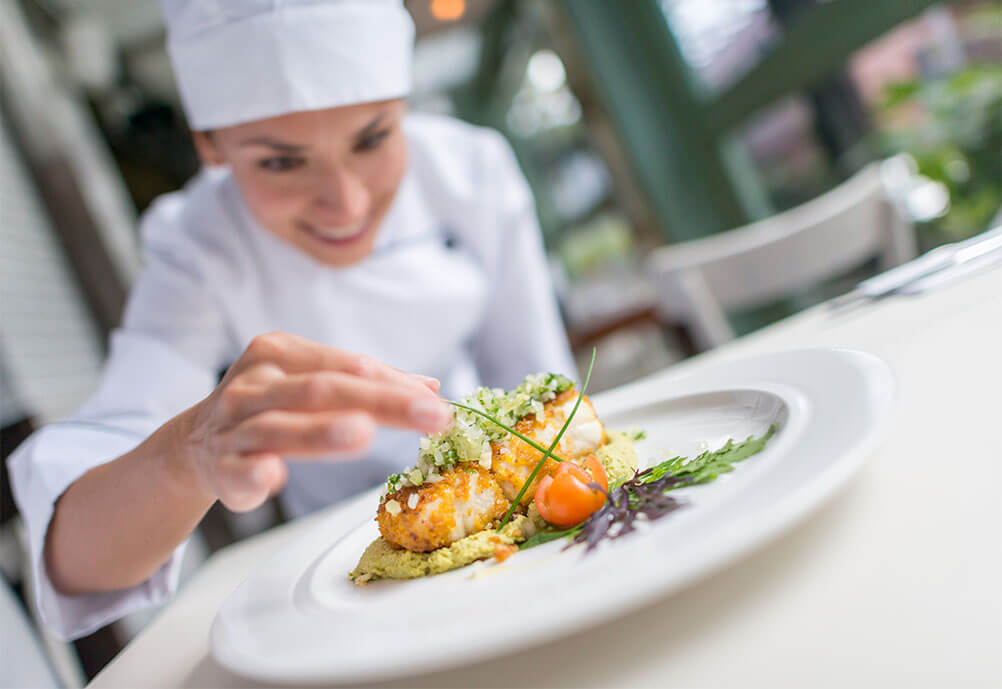Smiling female chef prepares a dish at a Michelin star restaurant