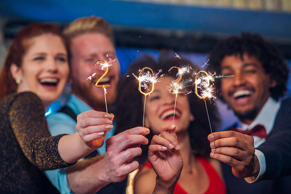 Group of friends celebrate the New Year's Eve with 2020 sparklers