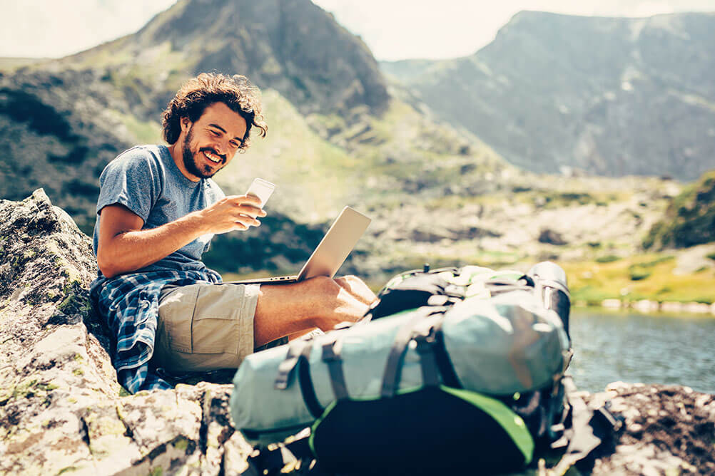 A man smiles as he works as a digital nomad from a beautiful location next to mountains and water