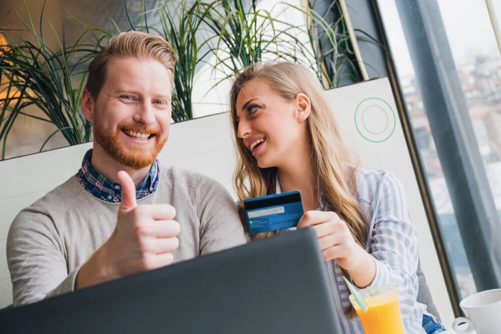 Smiling couple with credit card making online purchase